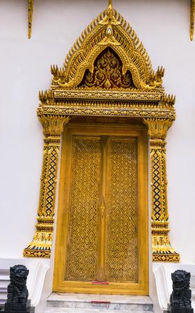 windows and doors: Ancient golden carving wooden door of Thai temple. Thailand