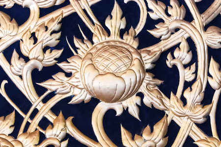 Gold Pattern of flower carved on temple wall background Stock Photo