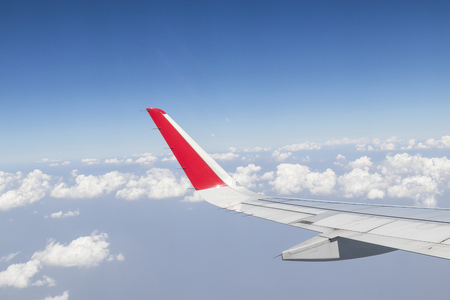 airplane wings in the blue sky with clouds
