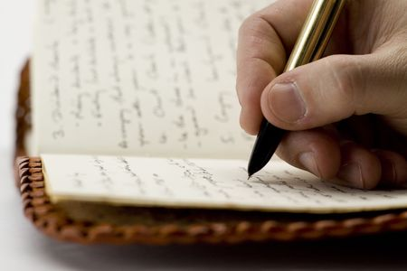 Writing in old book with pen Stock Photo
