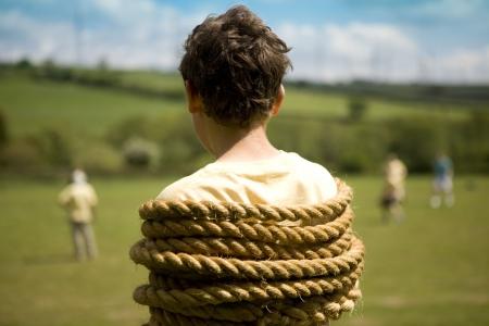 Young boy tied up with rope watching sport photo