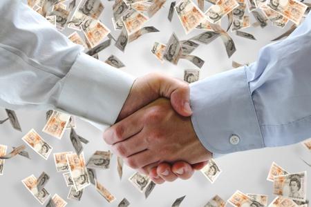 Business handshake with falling money