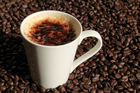 Cup of cappuccino with coffee beans Stock Photo