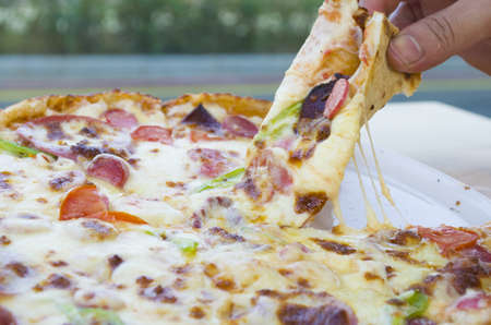 a slice of pizza in his hand a restaurant beautiful background Stock Photo