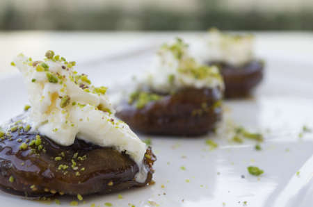 baklava: sweet fig with cream on white plate