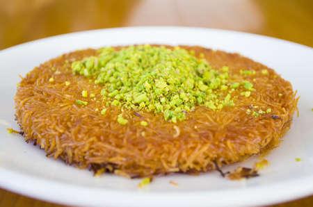 turkish dessert kunefe, kunafa, kadayif with pistachio powder and cheese hot eaten a sweet