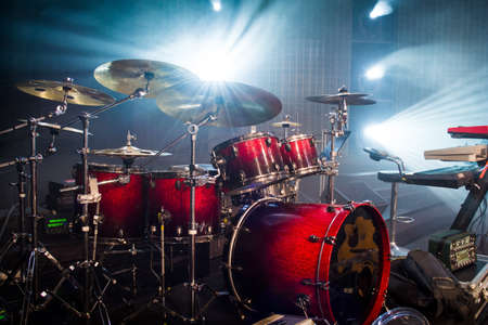drum set on stage and light background; empty stage with instruments ready for performance Archivio Fotografico