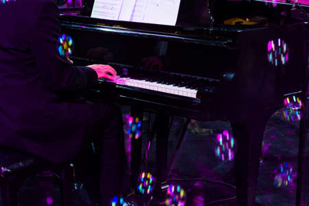 hand playing on piano in harsh concert lighting and colorfull bubbles Stock Photo