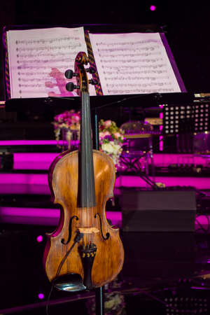 close up photo of vintage violin with bow and musical notes in concert hall
