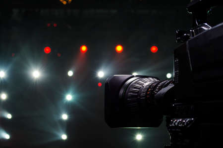 Professional video camera man film concert on stage.Big pro 4k video cam shoots live broadcast footage for television.TV camera operator shooting videos on concert stage Фото со стока