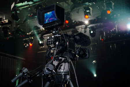 Professional video camera film concert on stage.Big pro 4k video cam shoots live broadcast footage for television.TV camera operator shooting videos on concert stage