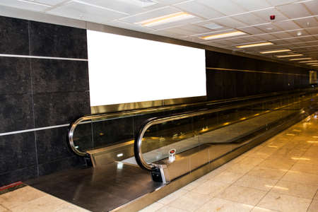 empty billboard and modern escalator at a international airport