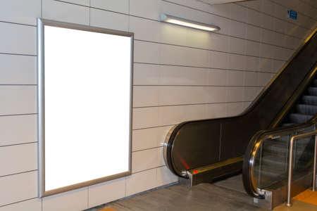 One big vertical  portrait orientation blank billboard with escalator background in public transport