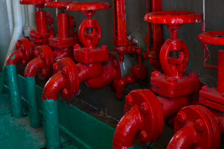 Red valve on the green pipe. Valve with wheel handle. Industrial gear. Close-up. Stock fotó
