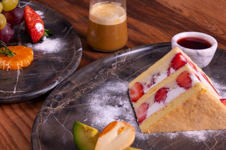 Strawberry cake, coffee and fruit plate on wooden table