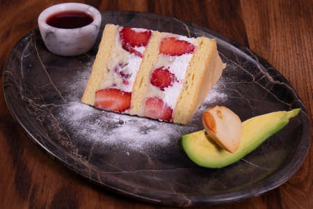 Strawberry cake and alligator pear in marble plate on wooden table