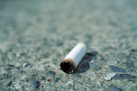 Cigarette butts in a sidewalk close-up. Imagens