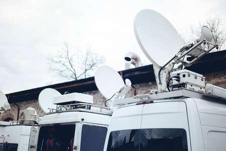 TV Media Television Trucks mit mehreren Satelliten-Parabolantennen und Glasfaserkabeln, die sich darauf vorbereiten, live über einen politischen Sport oder ein anderes Nachrichtenereignis zu berichten Standard-Bild