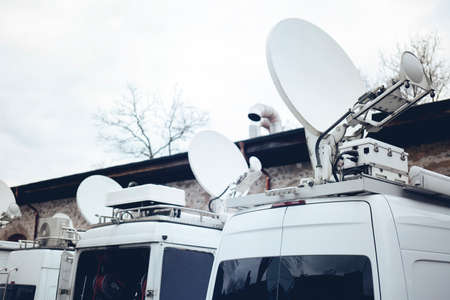 TV Media Television Trucks with multiple Satellite parabolic antennas and fiber optic cables preparing to report live a political sport or other news event 版權商用圖片 - 121143951