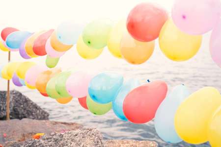 Colorful balloons on blue sky and sea background.