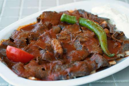 Kebab iskender turco tradicional sobre una superficie de madera en el restaurante. Foto de archivo