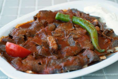 Traditional turkish iskender kebab on a wooden surface at restaurant. Imagens