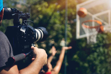 Blurry image of movie shooting or video production and film crew team with camera equipment at outdoor location and light flare effect.