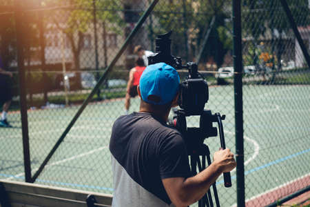 Verschwommenes Bild von Filmaufnahmen oder Videoproduktion und Filmteam mit Kameraausrüstung am Standort im Freien und Lichteffekt.