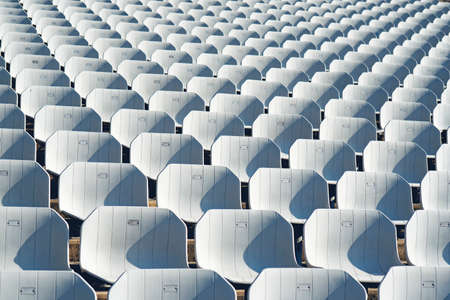 Rows of empty white plastic seats at the tribune in an open sports stadium