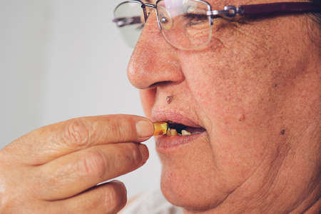 Vitamin And Supplement. Closeup Of Beautiful Old Woman Taking Yellow Fish Oil Pill. Female Hand Putting Omega-3 Capsule In Mouth. Healthy Eating And Diet Nutrition Concepts. High Resolution Image