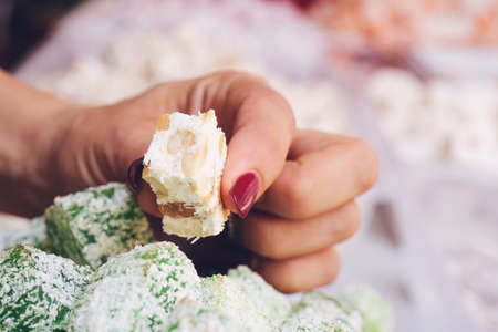 Woman hand holding Turkish Delight on colorful turkish delight background