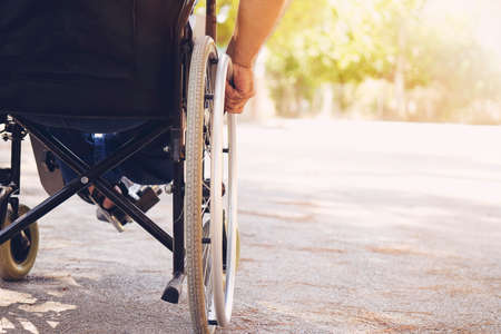 Closeup photo of Young disabled man holding wheelchair outside in nature
