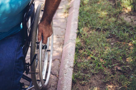 Close up photo of Young disabled man holding wheelchair outside in park