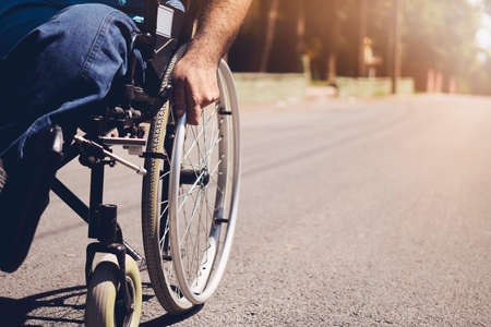 Disabled man on wheelchair in the outdoor park like other people, Close-Up his wheel, Life in the education age of special man, Happy disabled man concept. Stockfoto
