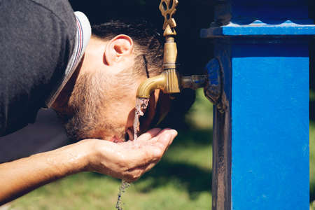 Caucasian young man preparing to drinking water from the retro fountain. Stockfoto