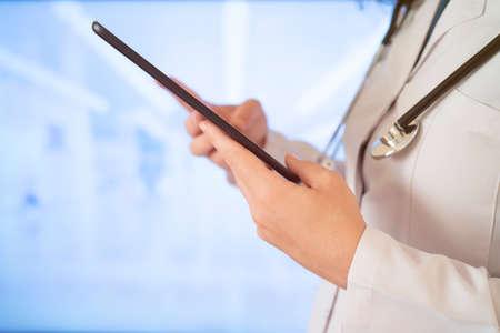 Kobieta lekarz korzysta z komputera typu tablet, stojąc prosto w szpitalu Zdjęcie Seryjne