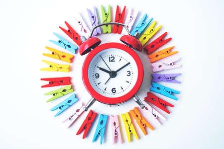 Concepto mínimo creativo de pinzas para la ropa en un círculo y un pequeño despertador en el medio sobre fondo blanco aislado Foto de archivo