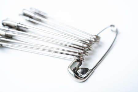 Macro metall safety pin for crafts, fashion, jewelry, hobby or household on white background with selective focus 写真素材