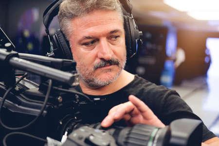 Cameraman professionista con cuffie con videocamera HD in diretta televisiva