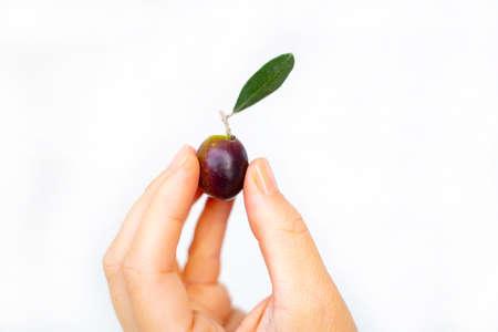 woman holding one olive isolated on white background Reklamní fotografie