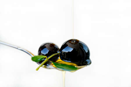 Olive oil over two olives branch in a spoon