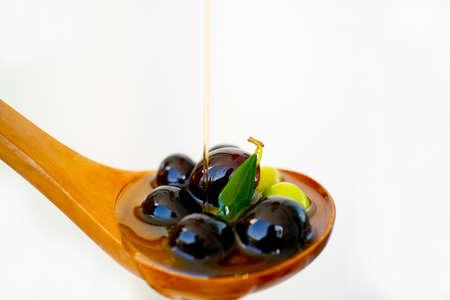 Olive oil jet over olives branch in a wooden spoon Reklamní fotografie