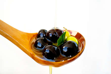 olive branch soaked in olive oil on a wooden spoon isolated on white background