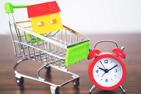 Small shopping cart and alarm clock on white background minimal creative concept