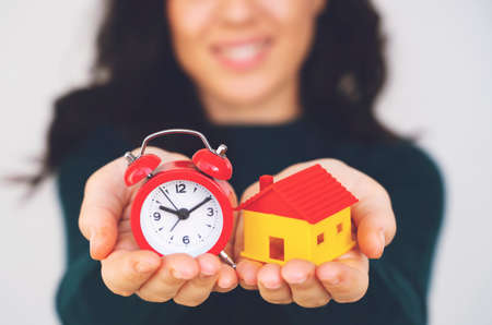 Woman hand holding house and alarm clock. house model for finance and banking concept. Reklamní fotografie