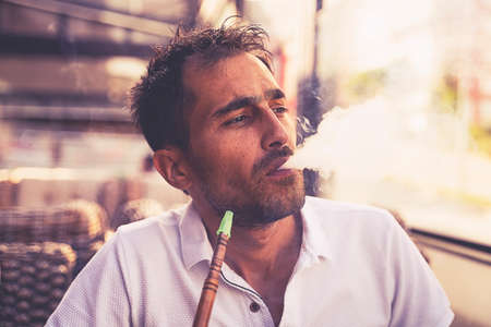 Close-up shot of a stylish adult guy smoking hookah indoor of a cafe