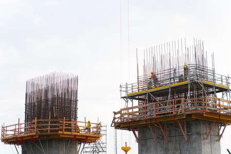Bridge widening construction project: Workmen ties reinforcing bars in concrete forms
