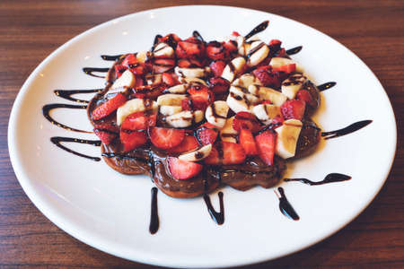 Traditional Belgian dessert - waffle with strawberry, banana and cream