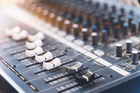 Sound mixer. Professional audio mixing console with lights, buttons, faders and sliders. Banco de Imagens