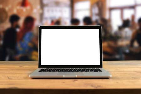 Maquette d'ordinateur portable à écran blanc sur une table en bois dans un espace de travail collaboratif. Café-restaurant